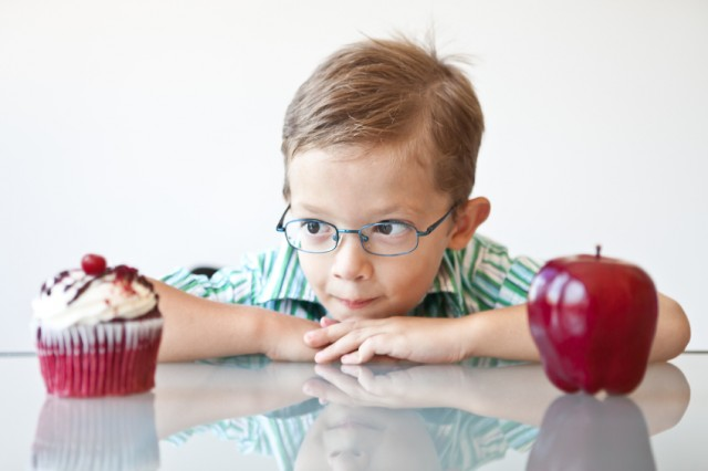 Little boy choosing between a cupcake and apple